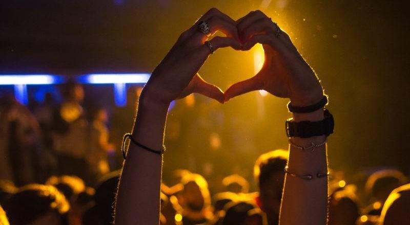 Hände in Herzform bei einem Konzert, das über eine Website für Eventbuchung entdeckt wurde.